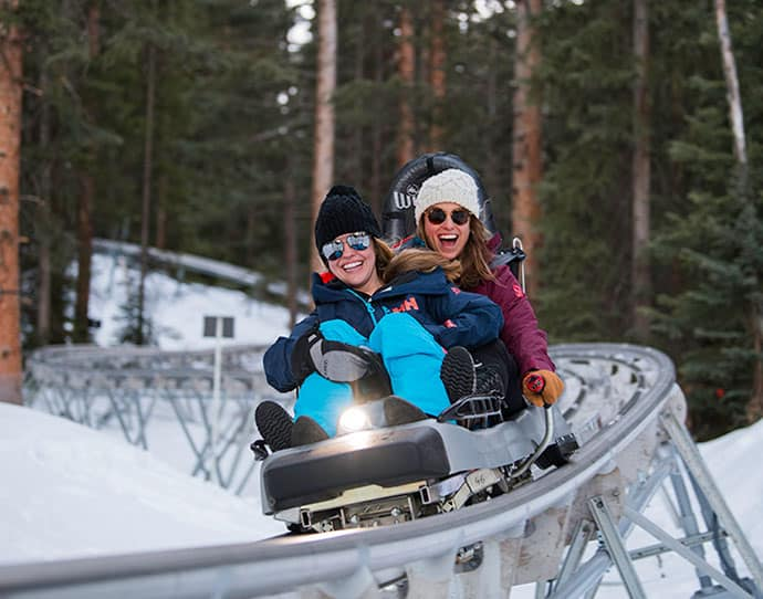 Friends riding Alpine Coaster in the winter in Snowmass, Colorado